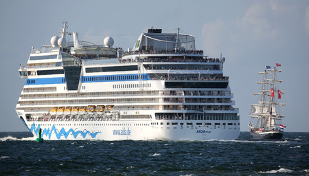 yachtsman: PORT WARNEMUENDE, GERMANY - AUGUST 09 German Cruise ship Aida mar and old dutch sailing ship Mercedes leave the port on 09 August, 2014 during the 24th annual Hanse-Sail event Mecklenburg-Vorpommern, Germany