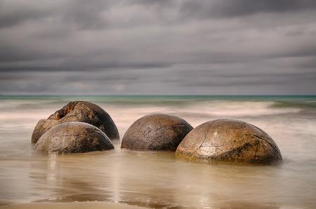 water waves: Moeraki Boulders near Hampden, New Zealand - long time exposure