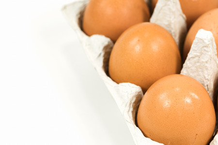 cardboard egg box with brown eggs isolated on white background Stock Photo