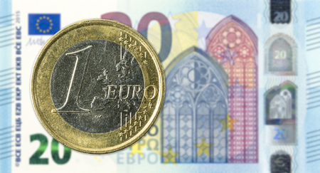 1 euro coins against 20 euro bank note obverse Editorial