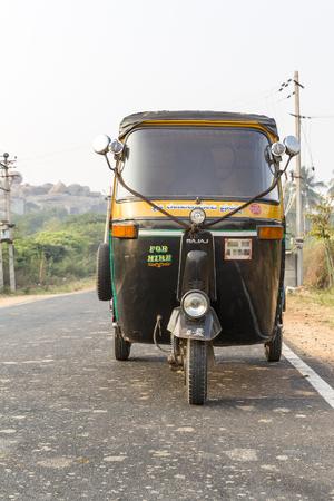 front of an auto rickshaw, tuk-tuk on the road, Hampi, Karnataka, India