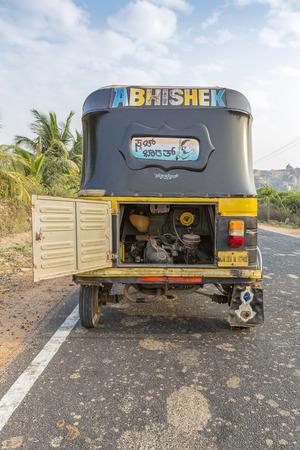 auto rickshaw seen from behind with open bonnet, tuk-tuk on the road, Hampi, Karnataka, India