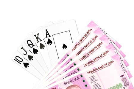 poker hand royal flush in spades and 2000 indian rupee bank notes isolated on white background