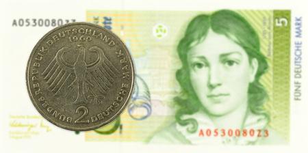 2 german mark coin agains 5 german mark bank note Standard-Bild - 102429602