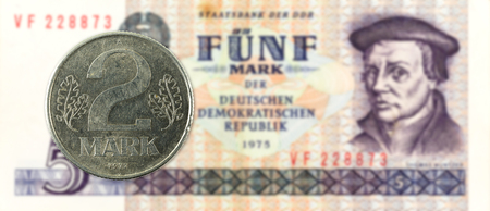 2 mark coin against historic 5 east german mark bank note