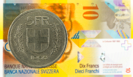 5 swiss franc coin against 10 swiss franc bank note