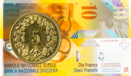 5 swiss rappen coin against 10 swiss franc bank note Banco de Imagens