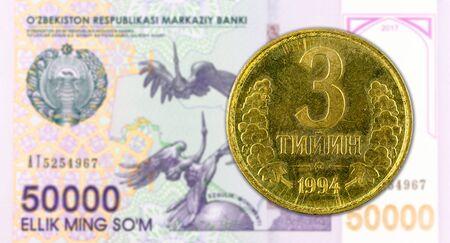 3 Uzbek Tiyin coin against 50000 Uzbek Som banknote Foto de archivo - 126599569