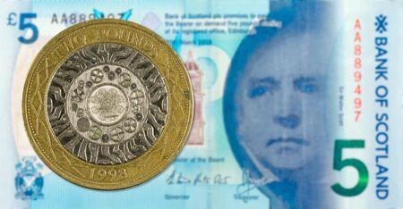 Moneta da 2 sterline contro una banconota da 5 sterline emessa dalla Bank of Scotland al contrario Archivio Fotografico