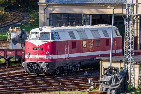 Löbau, Sachsen, Deutschland - 10.12.2019; rote historische Diesellokomotive wartet im Lokschuppen auf Wartung