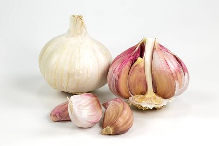 one closed white organic garlic bulb with skin and one opened semi-peeled garlic bulb and cloves isolated on white background