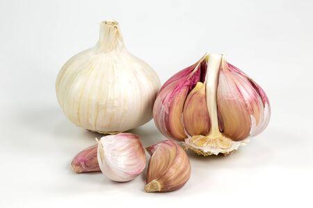 un bulbe d'ail biologique blanc fermé avec peau et un bulbe d'ail semi-pelé ouvert et des clous de girofle isolés sur fond blanc