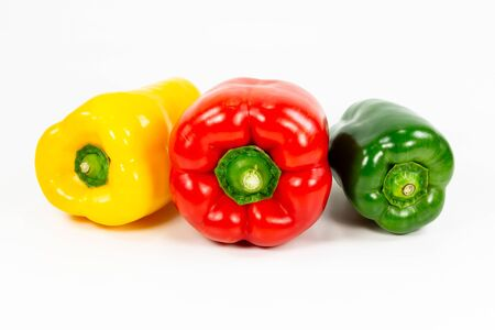 red, green and yellow capsicum fruit illustrating a healthy lifestyle isolated on white background