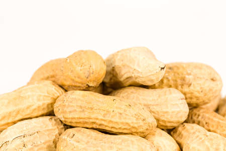 some dried and closed peanuts isolated on white background with copy space above