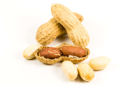 heap of dried, opened and closed peanut shells with nuts visible isolated on white background Standard-Bild
