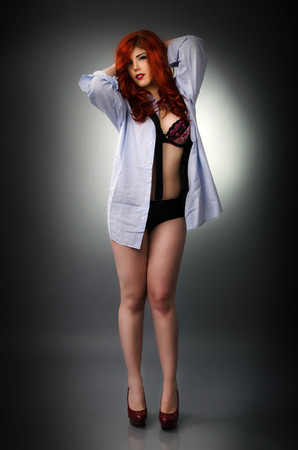 Sensual redhead woman wearing a men s shirt over her lingerie photo