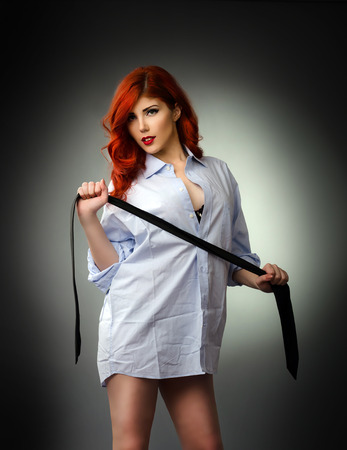 Redhead woman wearing a men s shirt and playing with a neck tie Stock Photo