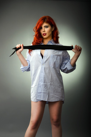 Sexy woman holding a men s tie ready for spanking photo