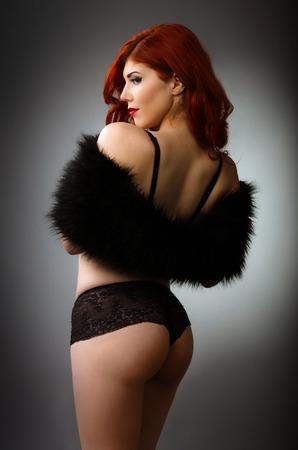 黒のランジェリーのセクシーな赤毛の女性 写真素材