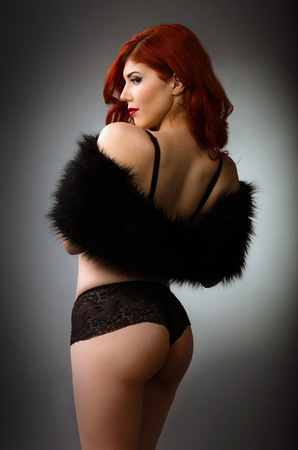 Sexy redhead woman in black lingerie Stock Photo
