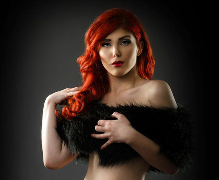 Sexy woman covering her breasts with a black fur coat photo