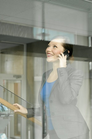 Business woman using a mobile phone at the office photo