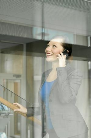 confianza: Mujer de negocios usando un tel�fono m�vil en la oficina