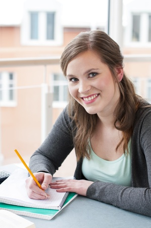 Portrait of female student studying at the table photo