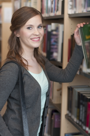 Portrait of female student selecting a book photo