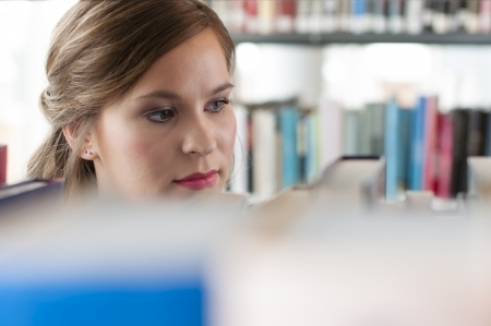 Portrait of female student selecting a book Stock Photo