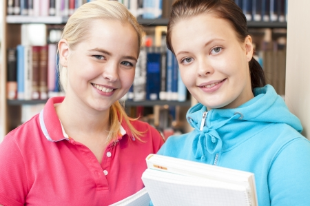 Two students in front of the bookshelf