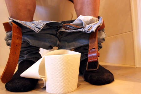 Adult male sitting on a toilet with pants down and a roll of toilet paper between his feet. Stockfoto