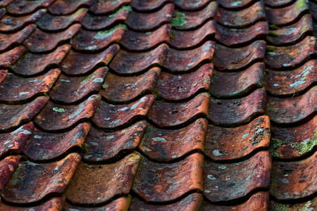Close-up of weathered old clay roof tiles in red or orange colors.