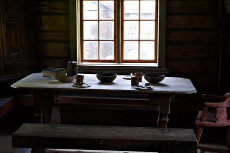 Medieval simple farmers dining table by the window with natural sunlight streaming in.