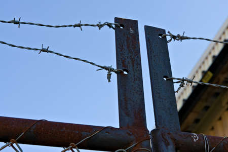 Rusted gate topped with barbed wire. High quality photo