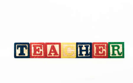 Wooden alphabet blocks spelling out the word Teacher, isolated on white background. High quality photo