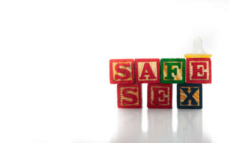 Wood alphabet blocks spell out the words SAFE SEX with a condom sitting on one block. Isolated on white background. High quality photo