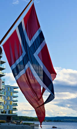Official Norwegian national flag waving in the wind with blue skies in the background.
