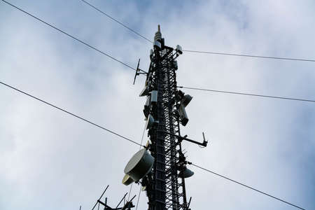 Large cellular communications tower with arrays, antennas and dishes for providing mobile connections as well as both 4G and 5G internet.