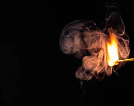 Single match catching on fire with puff of smoke surrounding it, isolated on black background . High quality photo Stock Photo
