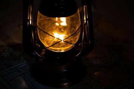 Vintage metal kerosene lamp lighting up a dark place with warm light. Standard-Bild