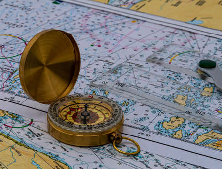 Vintage golden compass and a navigational ruler on nautical maps. High quality photo Stock Photo