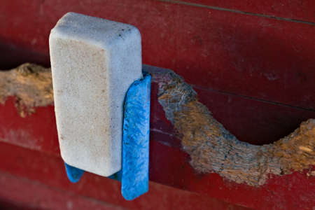A used salt block for farm animals hung on a red barn wall. . High quality photo