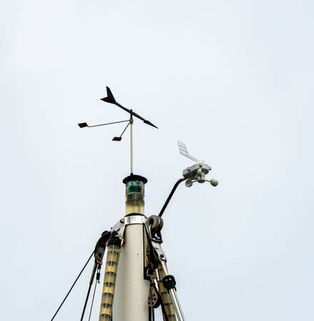 Top of the mast of a sailboat with wind indicator, lanterns, antennas and other instruments. High quality photo