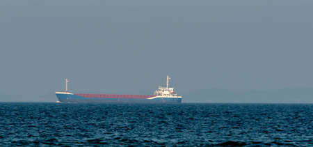 Blue cargo ship sailing on the ocean at a distance. . High quality photo