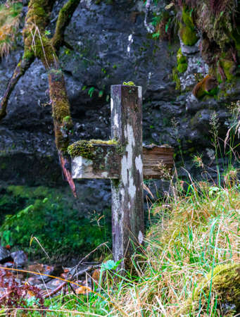 Old rotting and overgrown wood cross marking an unknown grave in a wild. . High quality photo