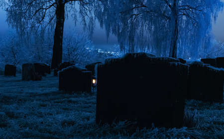Tombstones in a frozen graveyard on a cold winters night. High quality photo