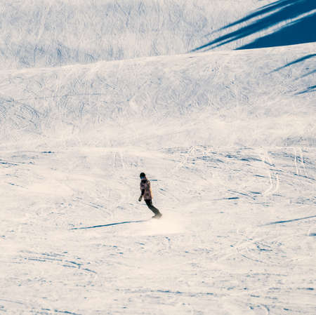 Lone snowboarder riding down a steep slope at an alpine sports resort. High quality photo