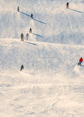 Skiers riding down a slope on a sunny day at a ski resort. High quality photo