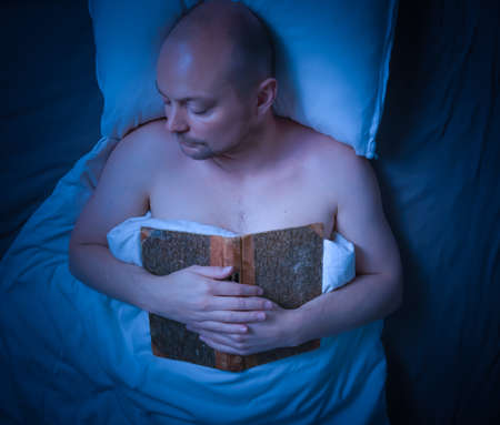 Man sleeping in bed after reading a book. High quality photo